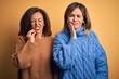 Middle age beautiful couple of sisters wearing casual sweater over isolated yellow background touching mouth with hand with painful expression because of toothache or dental illness on teeth. Dentist