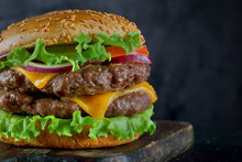 Burger With Two Beef Patties And Cheese On A Dark Background