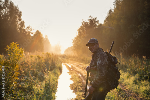 Silhouetted of a hunter with shotgun at beautiful sunset Fototapet