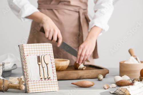 Obraz Woman with cook book preparing food in kitchen - fototapety do salonu