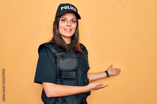 Fototapeta Young beautiful brunette policewoman wearing police uniform bulletproof and cap