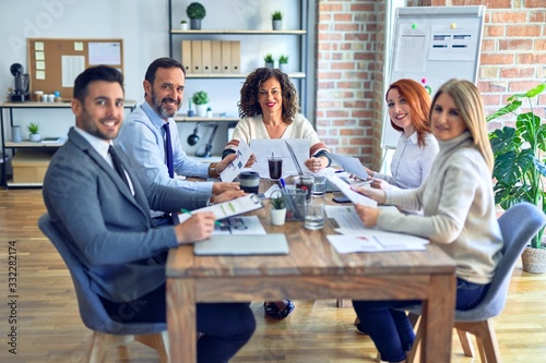 Obraz Group of business workers working together smiling happy. Sitting on desk posing with smile on face looking at the camera at the office - fototapety do salonu