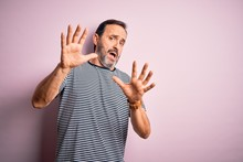 Middle Age Hoary Man Wearing Casual Striped T-shirt Standing Over Isolated Pink Background Afraid And Terrified With Fear Expression Stop Gesture With Hands, Shouting In Shock. Panic Concept.