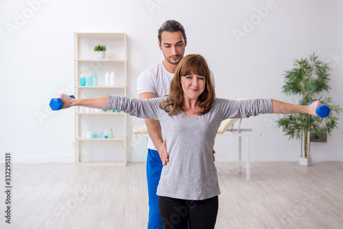 Obraz Young woman doing sport exercises with personal coach - fototapety do salonu