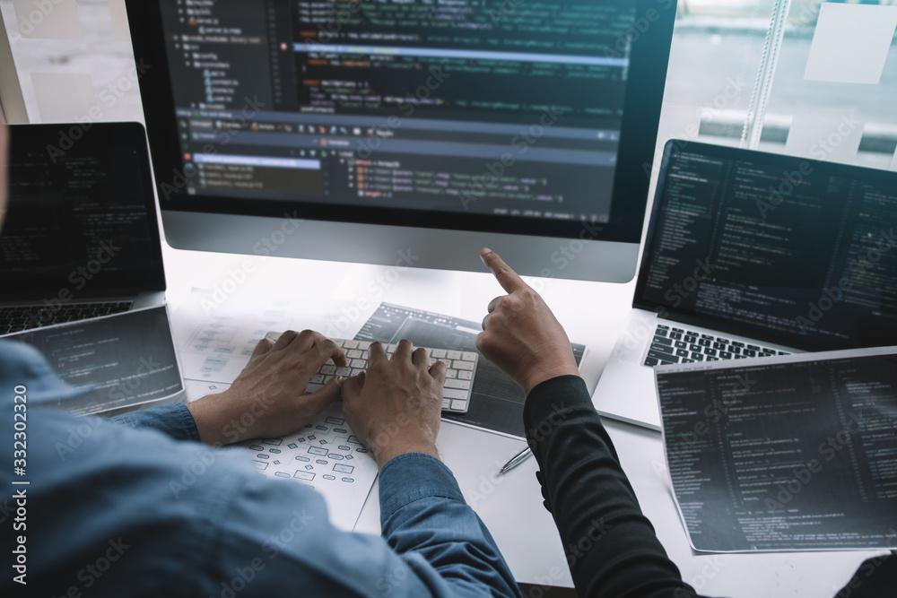 Fototapeta Professional development programmer cooperating meeting programming website working a software in office room.