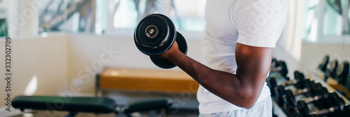 Fototapeta Young African American man standing and lifting a dumbbell with the rack at gym. Male weight training person doing a biceps curl in fitness center obraz