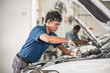 Asian mechanic Checking and repairing the car in maintainance service center which is a part of showroom, technician or engineer professional work for customer, car repair concept