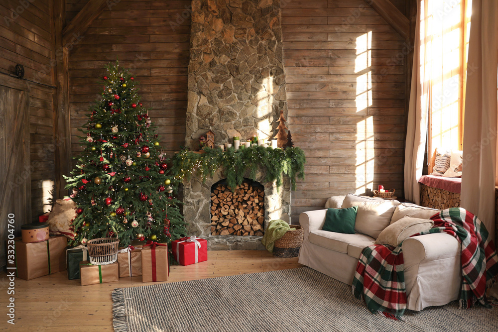 Fototapeta Festive interior with decorated Christmas tree and fireplace