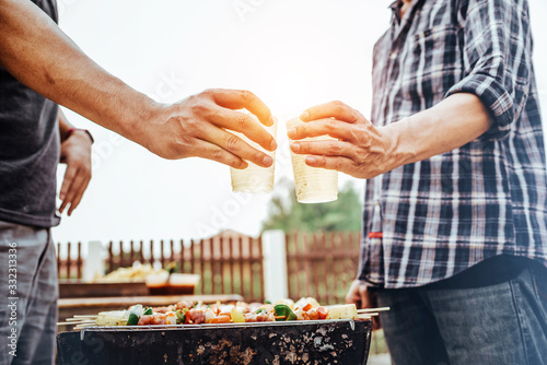 Happy man with friends making barbecue and drinking beer asian style Wallpaper Mural