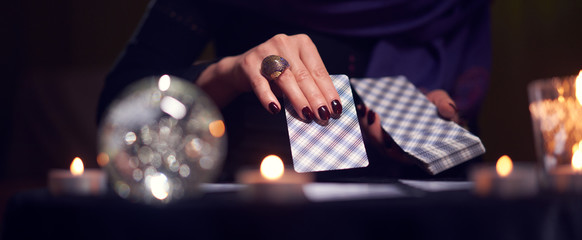 Close-up of fortuneteller's hands with cards at table with candles, magic ball in dark room