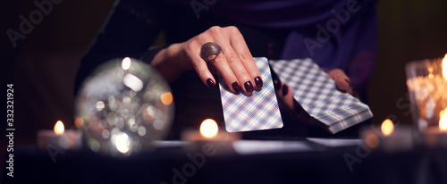 Obraz Close-up of fortuneteller's hands with cards at table with candles, magic ball in dark room - fototapety do salonu