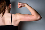 Sporty woman strains her biceps on gray background. Woman showing her strength.