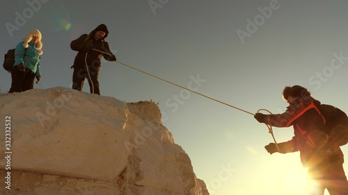 team of climbers climbs a mountain on rope Canvas Print