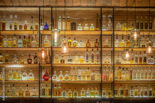 Fotografía Defocused background of bar counter with various bottles of alcohol