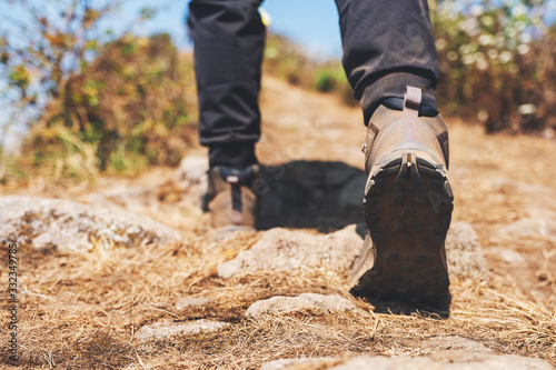 Fototapeta Closeup image of a woman hiking with trekking boots on the top of mountain obraz