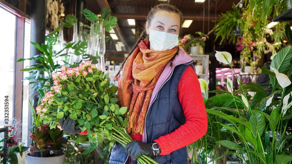 Fototapeta Florist employee in surgical mask protecting herself against COVID-19 coronavirus. Florist female looking into camera.