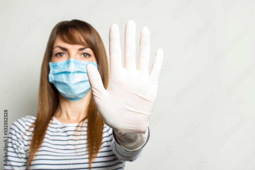 Fototapeta Young woman in a protective medical mask and latex gloves holds her hand and shows the viewer on a light isolated background. Concept of coronavirus, clean hands, no virus, stop. Banner. copy space
