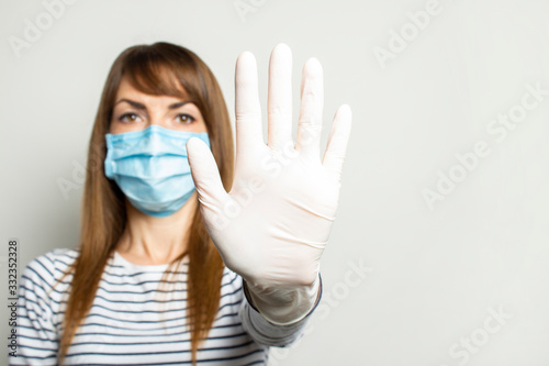 Obraz Young woman in a protective medical mask and latex gloves holds her hand and shows the viewer on a light isolated background. Concept of coronavirus, clean hands, no virus, stop. Banner. copy space - fototapety do salonu