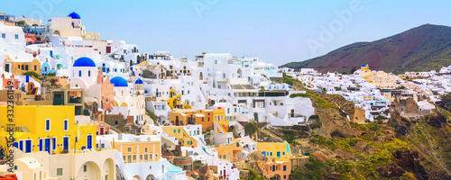 Fototapeta Oia, Santorini, Greece banner panorama of famous village town with white houses and blue domed churches obraz