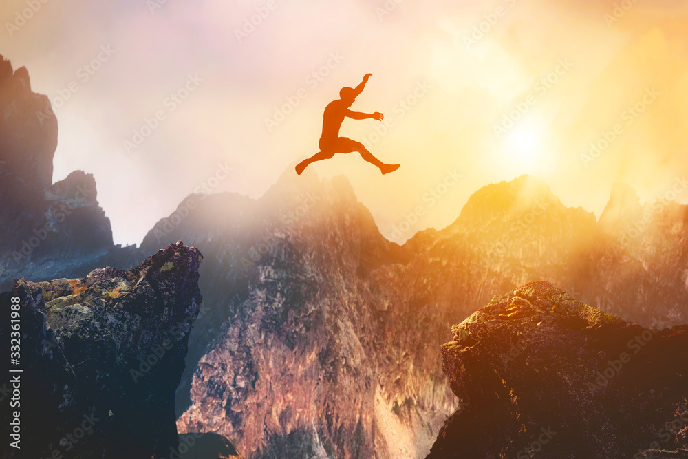 Fototapeta Man jumping between rocks. Overcome a problem for a better future