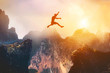 canvas print picture - Man jumping between rocks. Overcome a problem for a better future