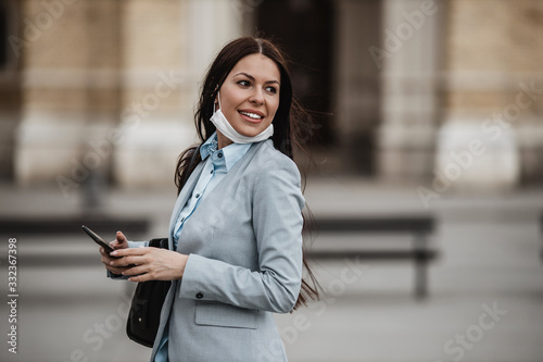 Photo Elegant woman walking on empty city street and wearing protective mask to protect herself from dangerous flu or virus