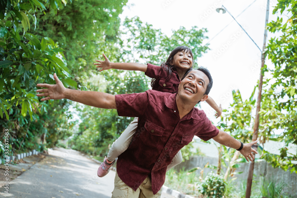 Fototapeta asian young father giving a daughter piggyback ride when playing in the park