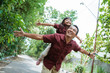 asian young father giving a daughter piggyback ride when playing in the park