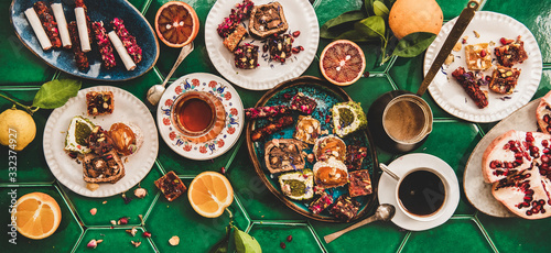 Fototapeta Flat-lay of variety of Turkish traditional lokum sweet delight with Turkish coffee in cups, tea in tulip glass and fresh fruits over green Moroccan tile table, top view. Middle East typical dessert obraz