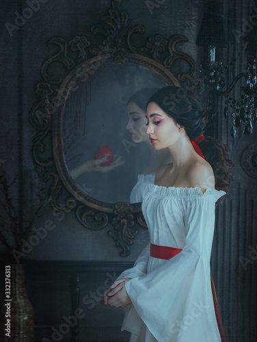 Portrait beautiful woman concept sleeping beauty fairytale Snow White. medieval clothes dress. Gothic princess makeup red lips. Ghost female hand with poison apple is reflected vintage antique mirror - 332376313