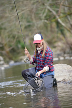 Woman Catching Rainbow Trout F...