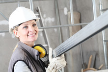 Smiling Woman Construction Worker Builder Portrait Wearing White Helmet And Hearing Protection Headphones, Holding A Metal Stud For Drywall On Interior Site Building Background With Scaffolding