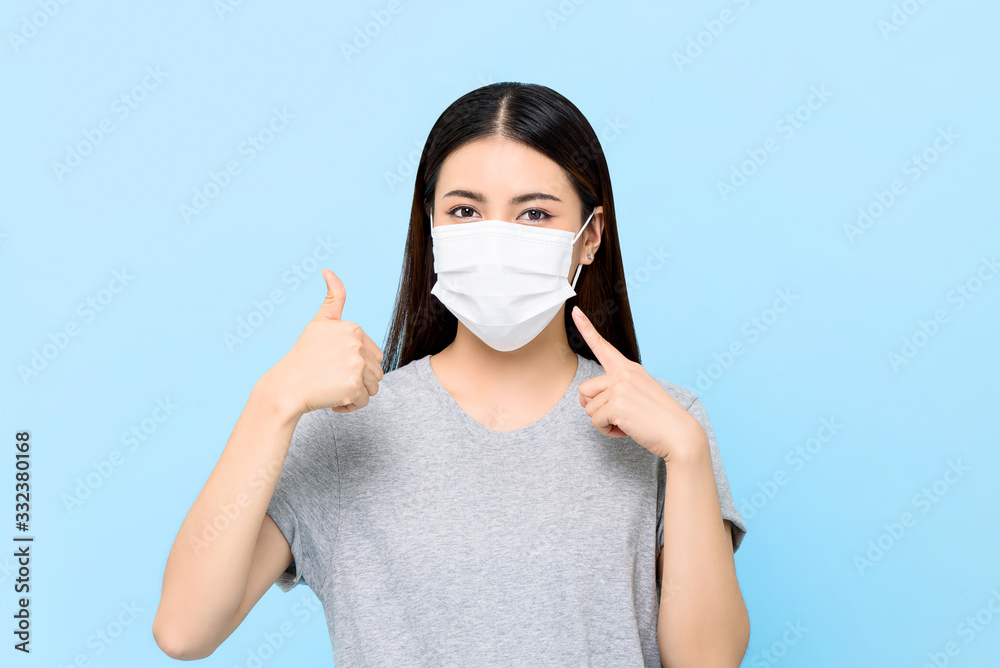 Fototapeta Young Asian woman wearing face mask to protect from COVID-19 and giving thumbs up isolated on light blue background