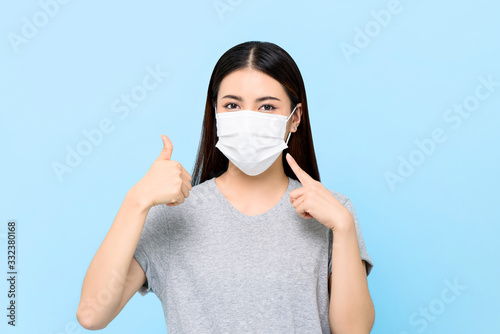 Obraz Young Asian woman wearing face mask to protect from COVID-19 and giving thumbs up isolated on light blue background - fototapety do salonu