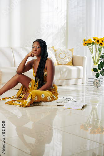 Young beautiful woman sitting on the floor in her living room and looking at cam Canvas Print