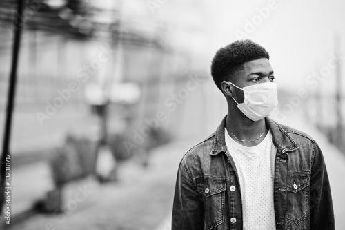 Fototapeta African man at park wearing medical masks protect from infections and diseases coronavirus virus quarantine. obraz
