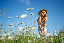 Woman In A Field With Flowers. A Young And Beautiful Girl Is Resting In A Chamomile Field.