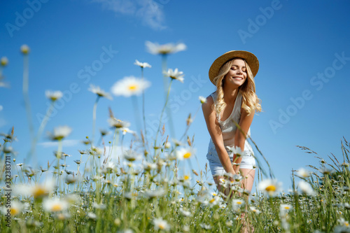Fototapeta Woman in a field with flowers. A young and beautiful girl is resting in a chamomile field. obraz