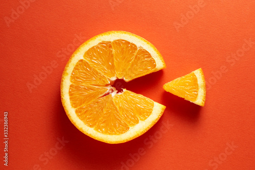 Fototapeta Orange slice symbolizing vitamin c is eating the cut out piece on orange background obraz