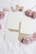 Wedding Stationery Mock-up Scene. Blank Greeting Cards, Envelope On Linen Tablecloth Background With Pink Blossoming Cherry Tree Branches And Ribbon. Feminine Still Life Composition. Flat Lay,vertical