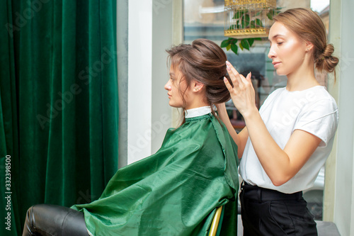 Hairdresser makes hairstyle.