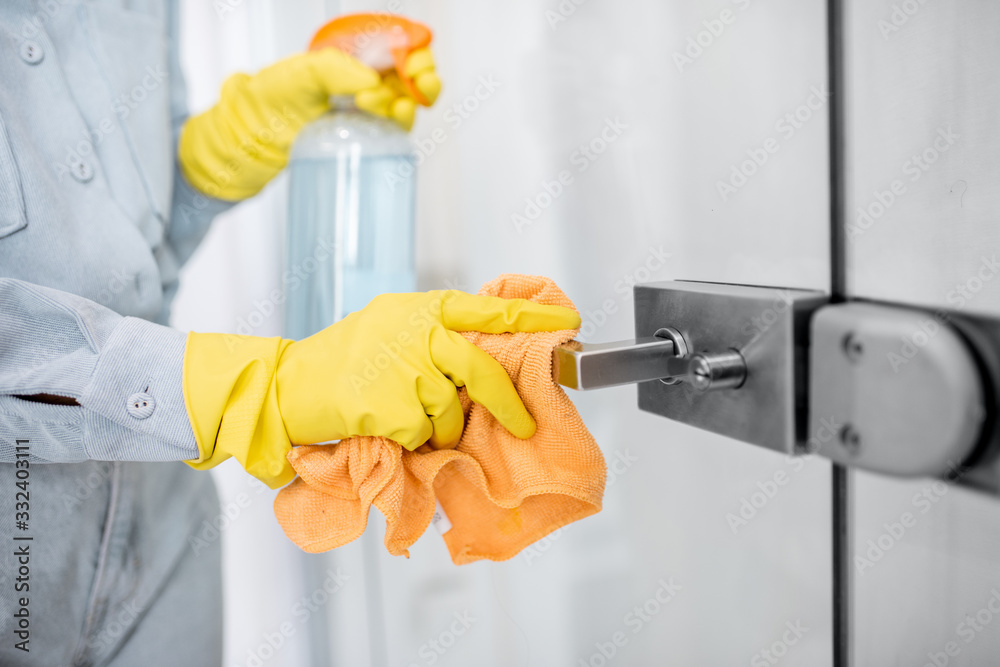 Fototapeta Woman in protective gloves disinfecting door handle while cleaning at home, close-up view on hands