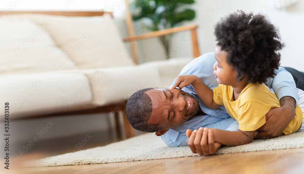 Fototapeta Happy African Father and little child son spending time playing at home together. Smiling Dad in blue shirt embracing or cuddling kid boy in yellow casual after arriving from working on wooden floor.