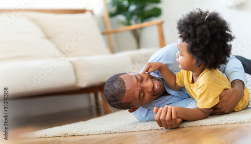 Fototapeta Happy African Father and little child son spending time playing at home together