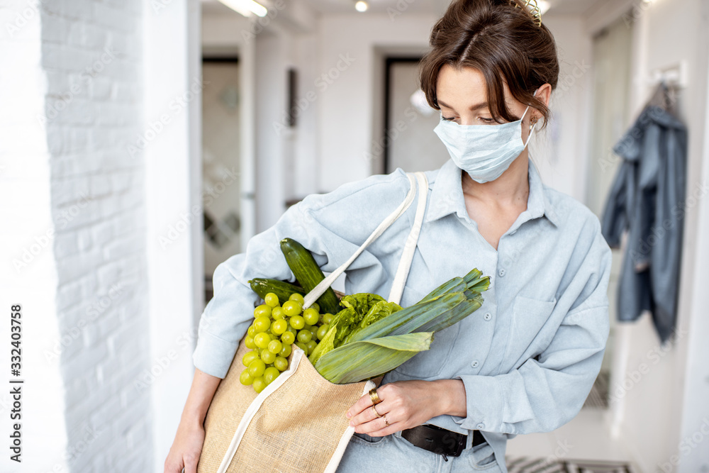 Fototapeta Young woman in medical mask coming home with shopping bag full of fresh food. Concept of lifestyle during an epidemic or bad air pollution