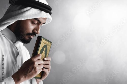 Fotografiet Religious arab muslim man holding holy quran