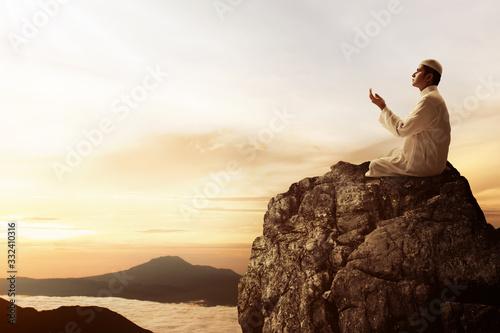 Religious asian muslim man praying on top of mountain Wallpaper Mural