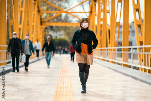 Valokuva A reckless young Woman walk on crowded street with a mask in a quarantine period because of pandemic global danger