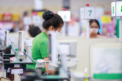 Cuadros en Lienzo Cashier or supermarket staff in medical protective mask working at supermarket