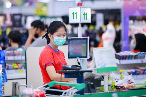 Fototapeta Cashier or supermarket staff in medical protective mask working at supermarket. obraz